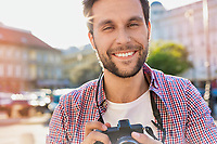 Young attractive man holding camera and taking photo