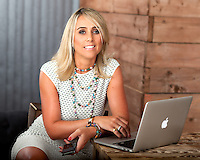 Relaxed corporate portrait featuring business woman taken in cool wine bar with raw wood panels and Mac Pro laptop on table