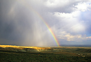 Rainbow and storm over the Honeycomb Buttes Wilderness Study Area in the Red Desert. Great Divide Basin, Wyoming