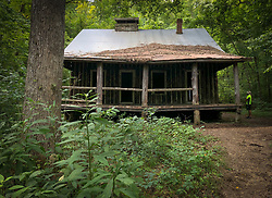 "A visitor looks at the abandoned log cabin near Pulltite Spring along the Current River, one of two rivers that make up the Ozark National Scenic Riverways in Missouri. The cabin (note the vertical log construction) was built as a ""retreat"" for early 20th century visitors who came to float the Current River. The Current River is the most spring-fed of all the rivers in the Missouri Ozarks. The river is a favorite with paddlers who enjoy the cold crystal clear water from springs that feed the Current River, including Cave Spring, Pulltite Spring, Round Spring, Blue Spring, and Big Spring. The scenic river is lined with rock ledges, caves, gravel bars and bluffs.<br /> <br /> The Ozark National Scenic Riverways was established in 1964, making it America's first national park area to protect a wild river system. The Ozark National Scenic Riverways, which include the Current and Jacks Fork rivers, is known for its caves, springs, sinkholes and losing streams. Visitors can enjoy water activities, such as floating, canoeing, tubing, swimming, and fishing. Additionally, there are opportunities for hiking, horseback riding, and wildlife viewing. Over 130 miles of waterways and 300 identified caves exist within the park."