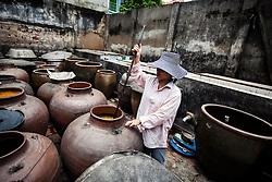 A Vietnamese woman stirs paste used to make vermicelli, Cu Da village, Hanoi, Vietnam, Southeast Asia