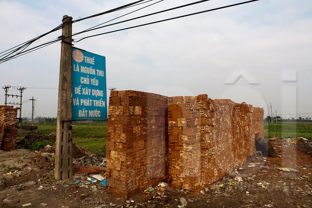 """propaganda next to a brick stack. """"paying taxes help construction and development of the country"""""""
