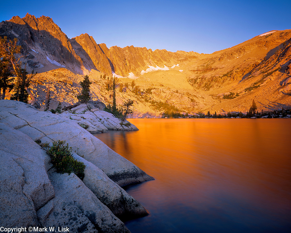 Warm light washes over the tranquil water of Lucille Lake high in the Sawtooth Wilderness.