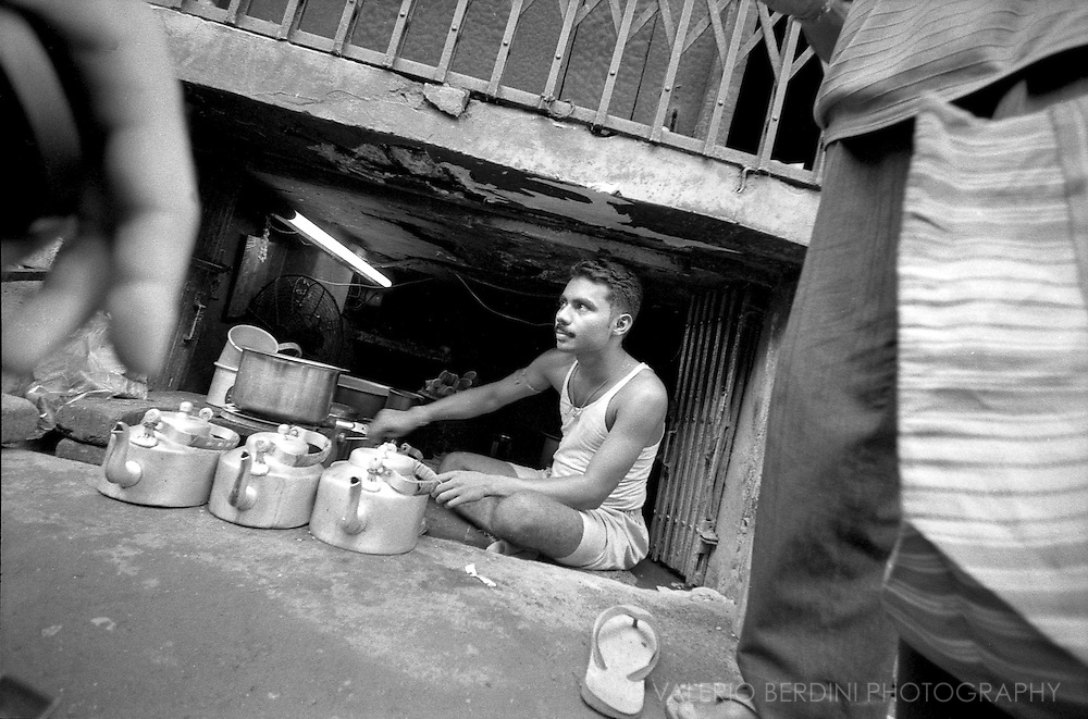 A men and his tea shop in a cavity below an elevated pavement. Passers by stop to drink chai.