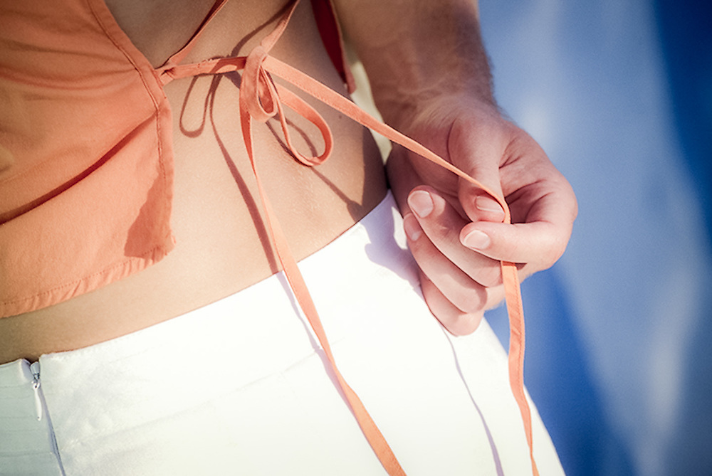 Male hands gently pulls on woman blouse string