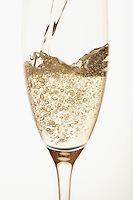 Champagne being poured into glass close up in studio