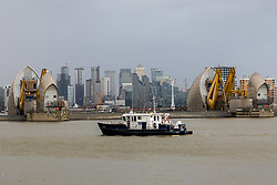 © Licensed to London News Pictures. 10/02/2020. London, UK. A Port of London Authority (PLA) boat is seen on the River Thames as flooding is seen at the Thames Barrier in London which is seen closed this afternoon at high tide to protect the capital from flooding during Storm Ciara. The Thames Barrier prevents the floodplain of most of Greater London from being flooded by exceptionally high tides and storm surges.  Photo credit: Vickie Flores/LNP