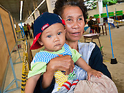 26 JUNE 2011 - CHIANG MAI, THAILAND:  A woman holds her grandson while she waits to cast her absentee ballot in Chiang Mai, Thailand, Sunday. Absentee voting was Sunday, July 26 in Thailand's national election. The regular voting is Sunday July 3. In Chiang Mai, center of the powerful Red Shirt opposition movement and their legal party Pheua Thai, turnout was heavy despite a steady rain. Thailand's democracy will be tested in the election, which is the most bitterly fought contest in Thai political history. The Pheua Thai represents people loyal to fugitive former Prime Minister Thaksin Shinawatra, ousted by a military coup in 2006. The ruling Democrats have governed Thailand in one form or another nearly continuously since 1932. Pre-election polls show Pheua Thai leading but not by enough to rule without forming a coalition with smaller parties.  PHOTO BY JACK KURTZ