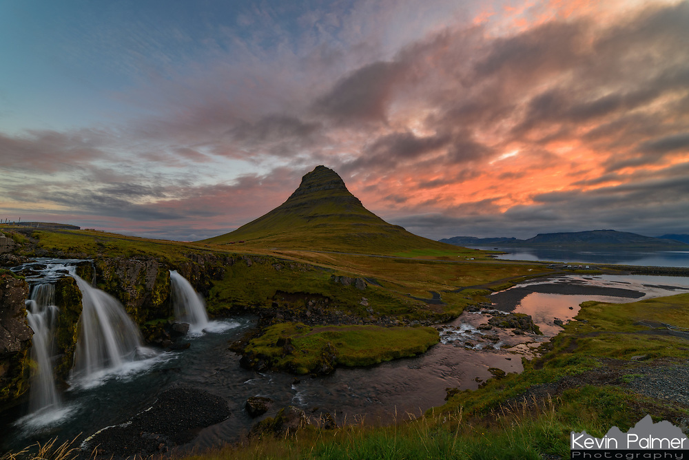 "Kirkjufellsfoss is one of the most iconic scenes in Iceland. Just Google ""Iceland"" and see how many times it shows up. The name translates to ""church mountain waterfall"" because of the peak's nearly perfect symmetrical shape. There is a trail (if it can be called that) leading to the top of Kirkjufell which is one of the steepest I've ever hiked. In the evening, tour buses stop here and this small spot is filled with hordes of tourists and photographers lined up tripod to tripod to capture the sunset. But I wanted to avoid that so I came back in the morning when it was much quieter. There was a storm moving in and the sunrise didn't look very promising. But the eastern sky took on an orange glow for a short time."