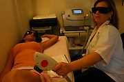 Laser hair removal. Woman undergoing Plasmalite laser cosmetic treatment to remove unwanted hair from her body. Both she and the laser operator are wearing goggles to protect their eyes from damage by the laser. Plasmalite technology uses pulses of light focused through a handset by the operator onto the surface of the skin. The light causes the hair shaft and follicle to heat up, and eventually the follicle dies and the hair cannot regrow. Several treatments may be needed to remove hairs from a region entirely.
