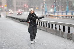 © Licensed to London News Pictures. 10/12/2017. London, UK. Two women walk across Tower Bridge during heavy snow fall. Heavy snow has fallen across the UK this morning. Photo credit: Vickie Flores/LNP