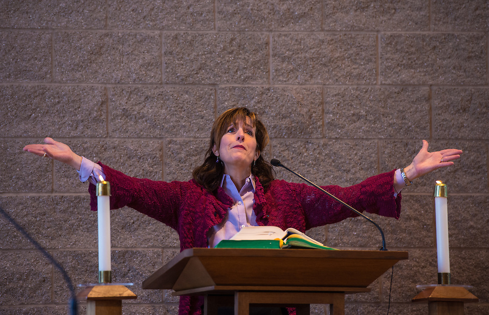 A cantor raises her arms to invite the congregation to sing during an Ash Wednesday liturgy at St. Matthew Church in Allouez, Wis. (Photo by Sam Lucero)