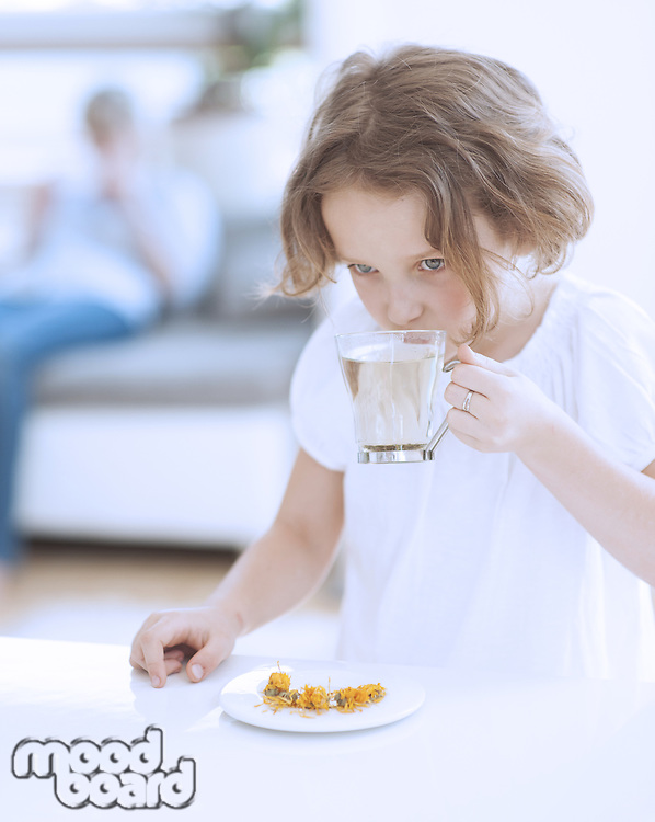 Young girl with cup of tea and flowers