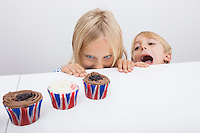 Tempted children looking at cupcakes on table