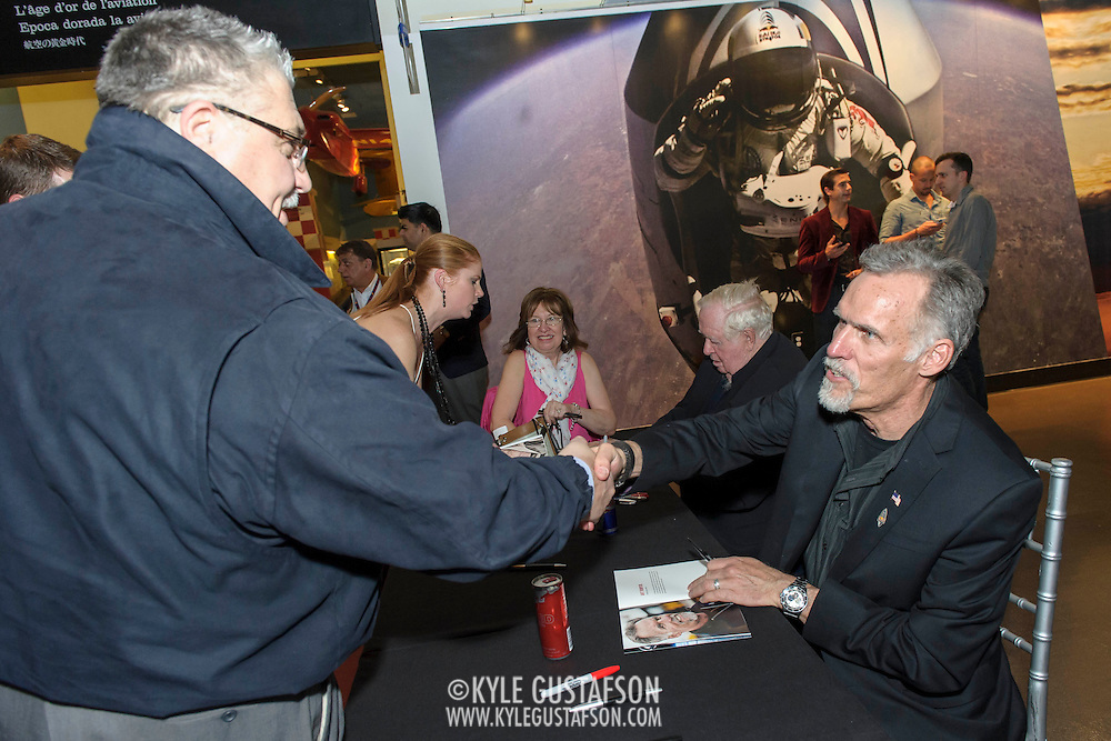 Attendees wait for the team members to sign special 'Stratos' editions of the Red Bulletin, at the Red Bull Stratos exhibit, at The Smithsonian National Air and Space Museum in Washington, D.C., USA on 1 April, 2014.