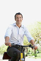 Businessman commuting by bike along tree lined road