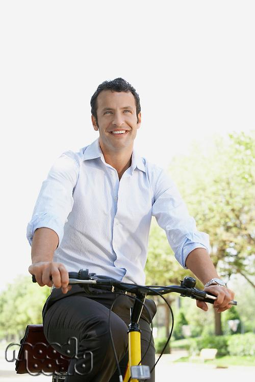 Businessman commuting by bike along tree lined road