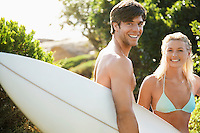 Young couple in swimwear man holding surfboard outside