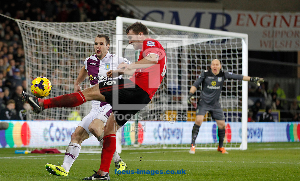 Ben Turner of Cardiff City and Nathan Baker of Aston Villa during the Barclays Premier League match at the Cardiff City Stadium, Cardiff<br /> Picture by Mike  Griffiths/Focus Images Ltd +44 7766 223933<br /> 11/02/2014
