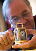 "© Licensed to London News Pictures. 23/10/2014. Guildford, UK. Michael Tooke changes the time on one of the smallest clocks on the premises, a miniature French porcelain panel carriage clock from 1880 made by Drocourt. . As British Summer Time comes to an end, staff at Horological Workshops start the task of changing the 100's of clocks at their store in Guildford, Surrey, UK. Michael Tooke who has owned the store for over 40 years and worked in the clock business all his life said. ""at this time of year we get a lot of people who bring clocks in for repair after they have changed the time incorrectly by winding back the hands manually"". Clocks change on Sunday morning 26th October. Photo credit : Stephen Simpson/LNP"