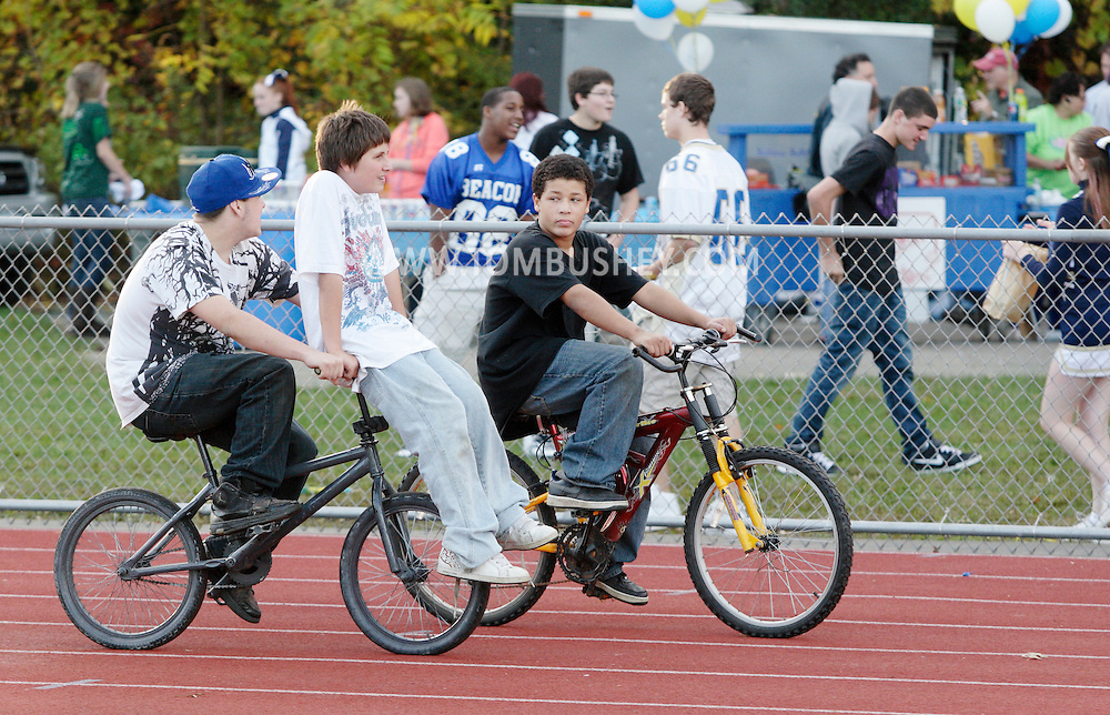 Beacon, New York - Three boys ride bicycles on the track after a high school football game on Saturday, Oct. 10, 2009.