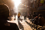 Commuters walk towards the early morning sunshine as they make their way to work on foot, bicycle, rickshaw and scooter through the narow streets of the Thamel District in Kathmandu, Nepal.