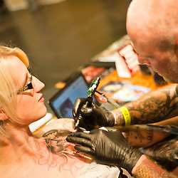 Manchester, UK - 4 August 2012: an artist creates a new tattoo on the chest of a woman during the Manchester Tattoo Show, one of the most popular conventions of the UK tattoo community.