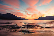 Alpenglow over the Chugach and Kenai Mountains and the tidal flats of Turnagain Arm in Southcentral Alaska. Summer. Evening.