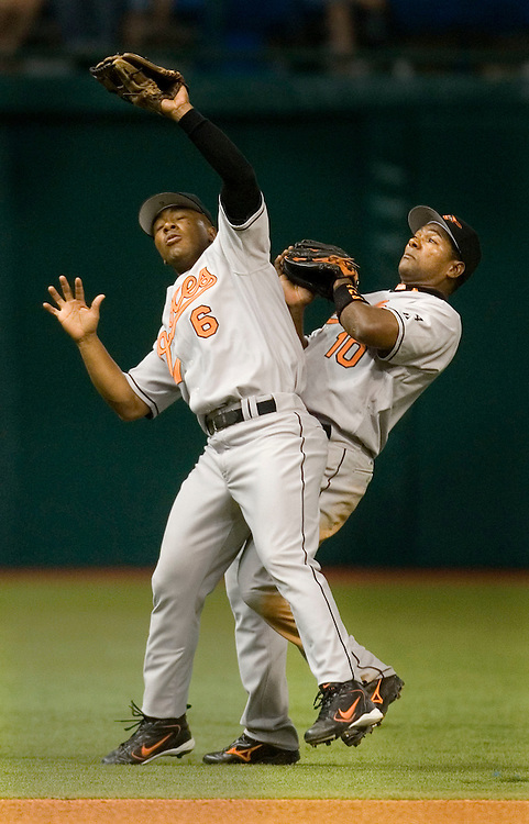 Baltimore Orioles Melvin Mora (L)  holds on to the ball for the out while colliding with teammate Miguel Tejada (R) after fielding a ball hit by the Tampa Bay Devil Rays' Travis Lee during the seventh inning of their American League game at Tropicana Field in St. Petersburg, Florida on April 10, 2006. REUTERS/Scott Audette
