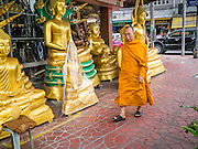 "12 NOVEMBER 2012 - BANGKOK, THAILAND:   A monk passes a shop on Bamrung Muang Street in Bangkok. Thanon Bamrung Muang (Thanon is Thai for Road or Street) is Bangkok's ""Street of Many Buddhas."" Like many ancient cities, Bangkok was once a city of artisan's neighborhoods and Bamrung Muang Road, near Bangkok's present day city hall, was once the street where all the country's Buddha statues were made. Now they made in factories on the edge of Bangkok, but Bamrung Muang Road is still where the statues are sold. Once an elephant trail, it was one of the first streets paved in Bangkok. It is the largest center of Buddhist supplies in Thailand. Not just statues but also monk's robes, candles, alms bowls, and pre-configured alms baskets are for sale along both sides of the street.    PHOTO BY JACK KURTZ"