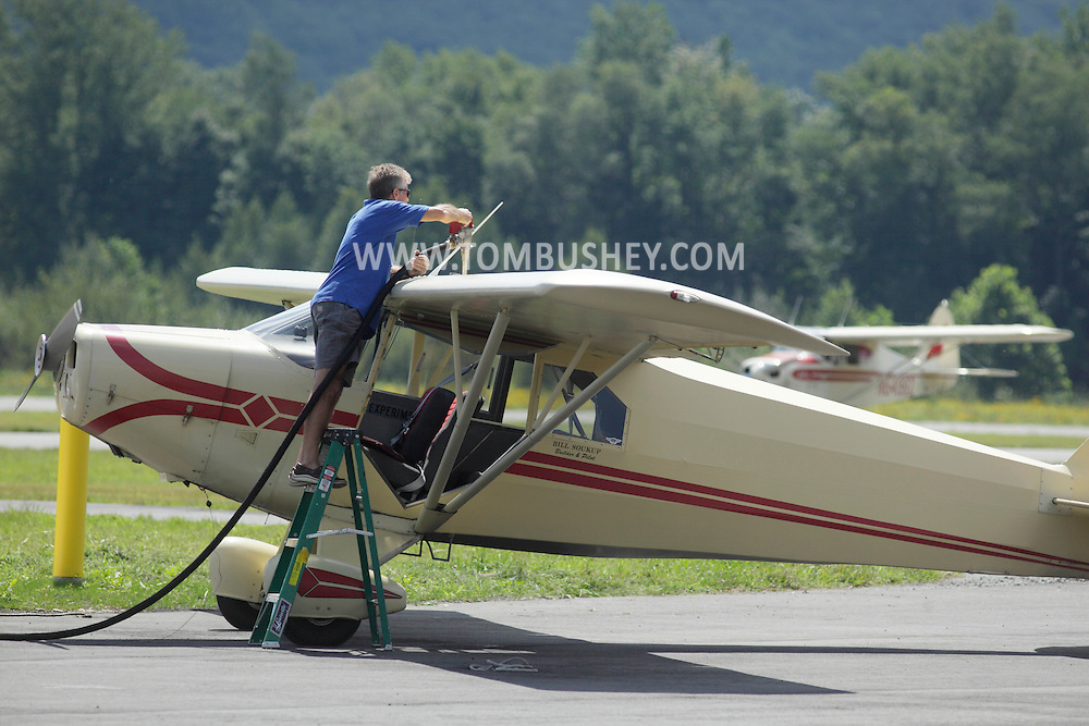 Wurtsboro, NY - A pilot uses a ladder to fuel his PA-14 single-engine plane at Wurtsboro Airport on Aug. 30, 2009.