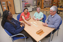 Group playing dominoes. Cleared for Mental Health issues.