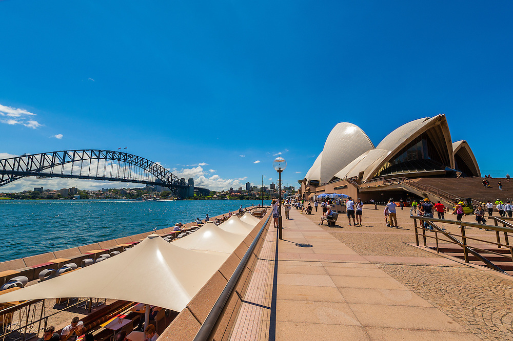 People enjoying the view of Sydney harbor from the Opera Bar (Sydney Opera House in background), Sydney, New South Wales, Australia