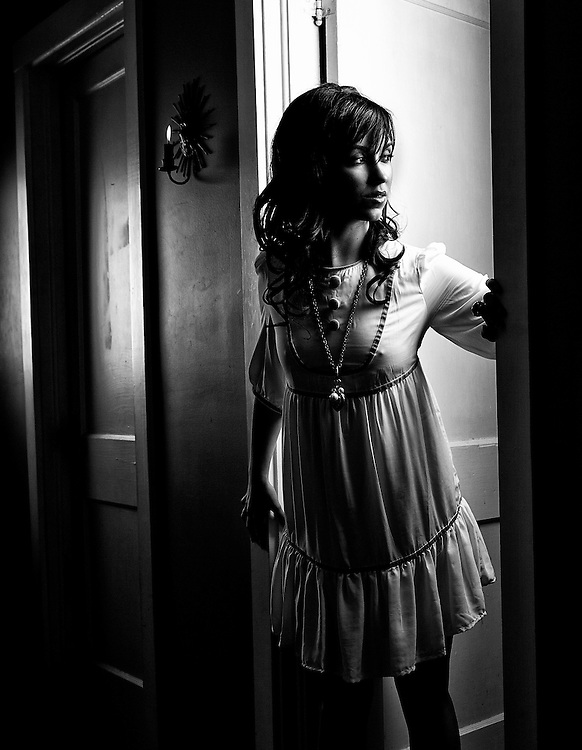 Dramatic image of a young woman in a home hallway.