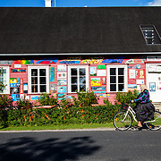 A woman biking in front of the Kihnu museum; the bike is the main mode of transportation on the island