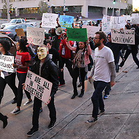 "Protesters march through downtown streets on the way to the Amway Arena, home of the Orlando Magic, to perform a ""die in"" to rally against police brutality on Wednesday, December 10, 2014 in Orlando, Florida.  Since a Staten Island grand jury decided last week not to bring any charges against a white officer who was seen on video using a chokehold on Eric Garner, and other use of questionable force issues by the police across the country, the Orlando protesters wanted to represent the city of Orlando.  (AP Photo/Alex Menendez)"