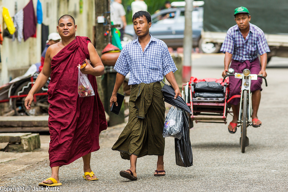 19 JUNE 2013 - YANGON, MYANMAR:  Buddhist monks walk down a residential street in Yangon. Most Burmese men join the Sangha (Buddhist clergy) at least once in their lives. Some for just a few weeks, others for years. Some, but not all, make a lifetime commitment.    PHOTO BY JACK KURTZ