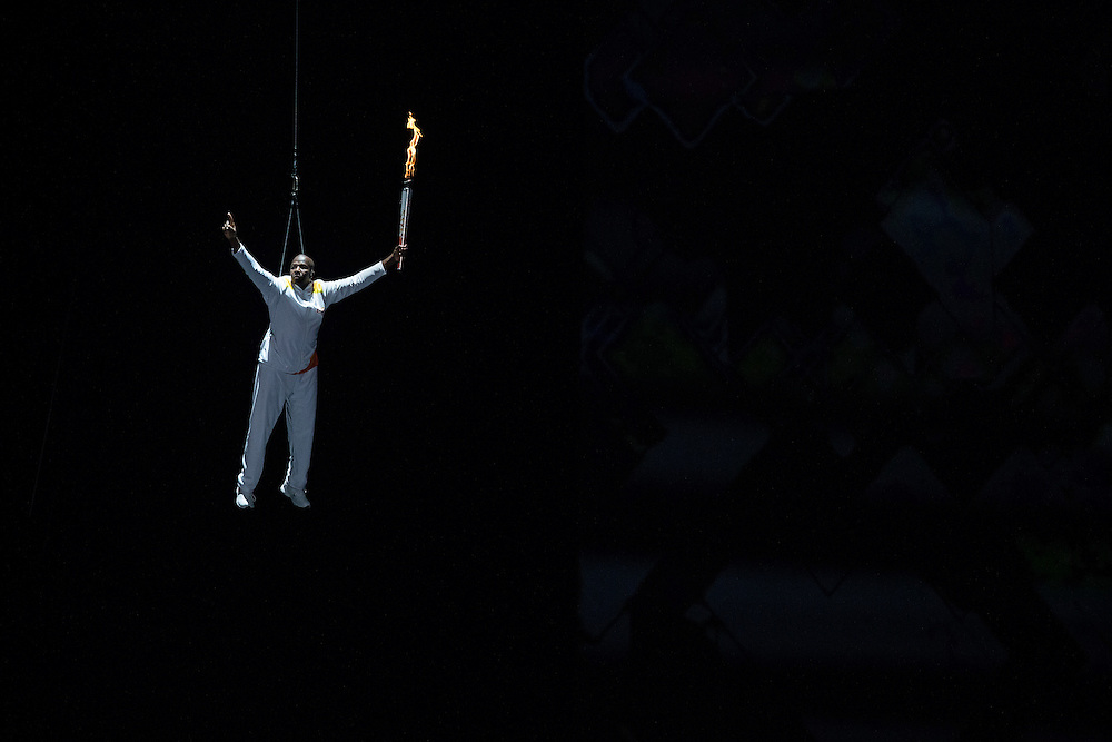 Donovan Bailey, Olympic gold medalist in the 100m, is lowered with the Pan American Games flag during the opening ceremonies at the 2015 Pan American Games in Toronto, Canada, July 10,  2015.  AFP PHOTO/GEOFF ROBINS