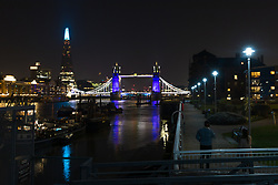 © Licensed to London News Pictures. 26/03/2020. London, UK. People look on as Tower bridge and the London Shard are illuminated in blue this evening in recognition and appreciation of National Health Service (NHS) staff working in hospitals across the country during the ongoing COVID-19 coronavirus epidemic. Photo credit: Vickie Flores/LNP