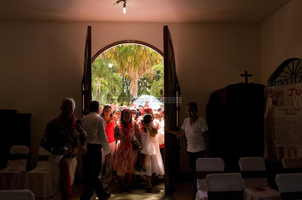 Las puertas de la Igesia de Curiepe son abiertas a los fieles que asisten a la misa de adoración a San Juan.  Tambores de San Juan, en la población de Curiepe, es una de  las celebraciones mas importantes de toda la región de Barlovento.  Sus tierras fueron asiento de haciendas de cacao en la Colonia.  La mayoría de la población de Barlovento fue traída de lo que actualmente constituye el Congo, Zaire y Angola (correspondiente al area cultural de la etnia africana Bantú, Loangos y Yorubas). Cuando los esclavizados fueron traídos para trabajar en las haciendas, les fueron prohibidas sus manifestaciones culturales y religiosas y les fueron impuestos nuevos cultos. Ante esta situación y al no tener otra opción que aceptar las imágenes del culto católico, le asignan a cada santo una deidad de su esquema religioso africano. Así, San Juan representa una de las más importantes en lo que, los expertos definen como un sincretismo de cierta compilación. Junio 24, 2010 (Gregorio Marrero/Orinoquiaphoto)