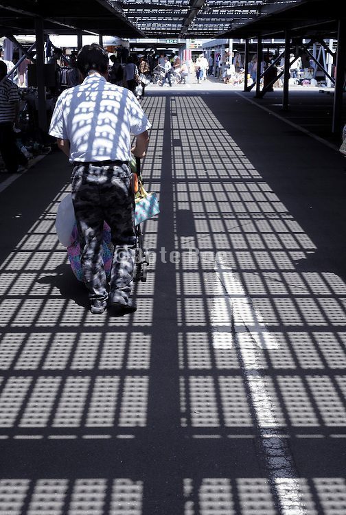 shadow of overhead metal grating projected on man with baby stroller