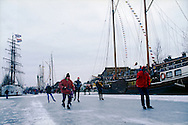 Nederland, Stavoren, 19970104..De Elfstedentocht in januari 1997 in Friesland..Schaatsers rijden door de polders.  Mensen staan te kijken naar de schaatsers die voorbij komen. 6000 schaatsers en meer dan een miljoen toeschouwers..Schaatsers komen binnen in de haven van Stavoren met zijn mooie schepen...The Elfstedentocht is a speed skating competition and leisure skating tour in the province of Friesland in the Netherlands..6.000 skaters and over a million spectators were present. The route takes the skaters through eleven cities in Frisia, in the North of Holland. Flag of the provence Friesland. 200 kilometre race along the frozen canals of Friesland..Skaters go along the harbour of the city Stavoren with it's beautiful boats frozen in the ice..