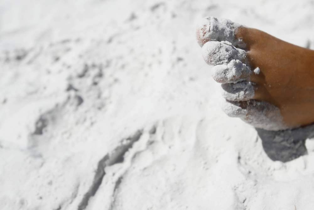 SIESTA KEY, FL -- August 22, 2009 -- The toes of Joe Mastro of Tampa are powdered with the cool, white sand at Siesta Key Public Beach on Siesta Key in Sarasota, Fla., on Saturday, August 22, 2009.  Siesta Key Beach is known for its soft white sand, which stays cool even in the dead heat of summer.  Summer is becoming a more popular time to visit Siesta Key out of season with shorter lines, cheaper rates, and more room to plop a towel and umbrella down in said sand.