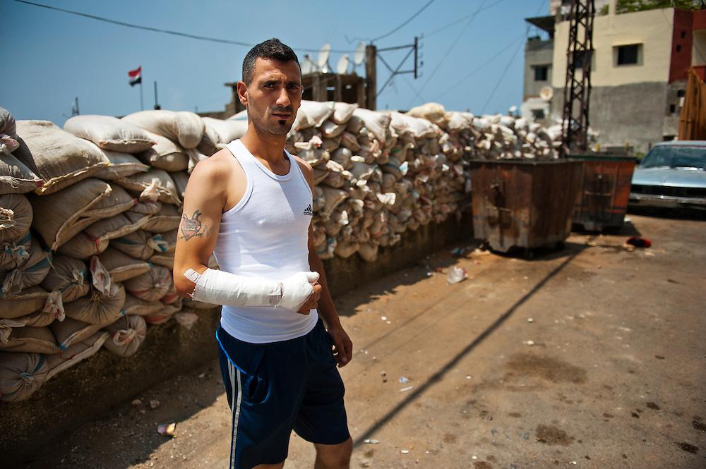 Alawite Jabal Mohsen neighborhood. Sandbags and fabric protect against Sunni snipers. Nader, an Alawite civilian, was wounded. A rifle grenade exploded near him while he was on his scooter...Quartier alaouite Jabal Mohsen. Sacs de sable et bâches protègent contre des snipers sunnites. Nader, un civil alaouite blessé. Une grenade a fusil a explosé près de lui alors qu'il était sur son scooter.