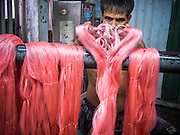 13 SEPTEMBER 2013 - BANGKOK, THAILAND: A worker in a Thai silk weaving workshop in a home in the Ban Krua section of Bangkok dyes silk threads. After the threads are dyed they are woven into silk. Many of the silk making families in Ban Krua are Cham Muslims from Cambodia who settled in Bangkok in the early 19th century after Rama I, the King of Siam at the time, offered them land in exchange for their services in a war against the Khmer (Cambodia) empire. The late Jim Thompson, founder of Jim Thompson Thai Silk, first made the silk weavers famous when he bought most of his silk from them.         PHOTO BY JACK KURTZ