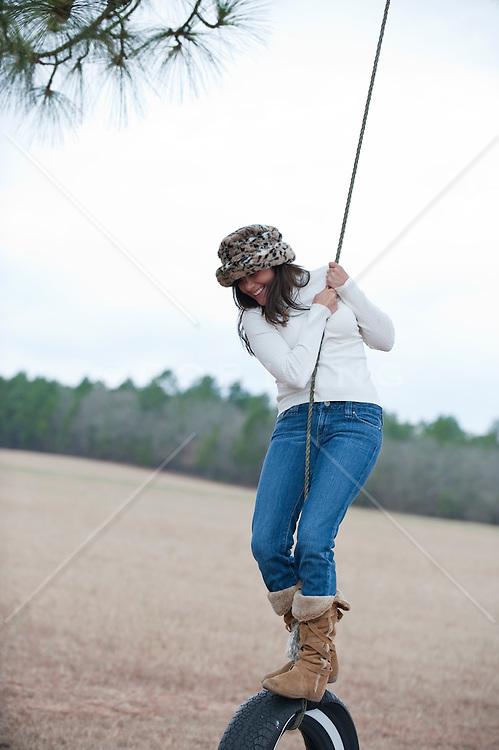 girl standing on a tire swing in Aiken, SC