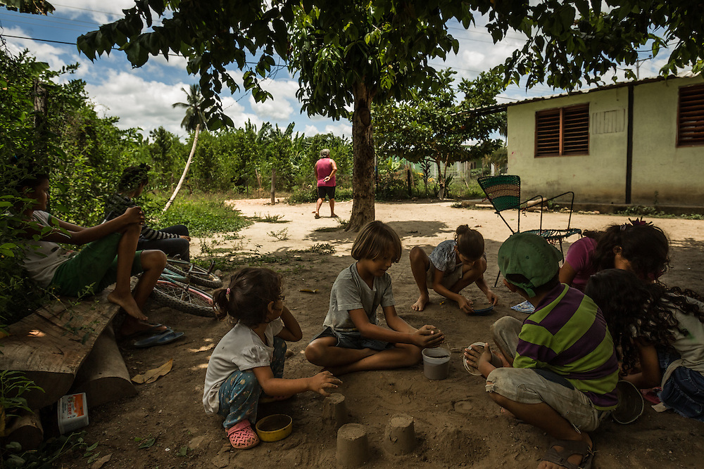 BARALT MUNICIPALITY, VENEZUELA - AUGUST 28, 2014: Children play with neighbors in the dirt in the yard of their humble home near  oil wells in the Baralt municipality of Zulia state. Despite being so close to wells that have brought Venezuela tremendous oil wealth, the streets are unpaved and people live in shacks made from corrugated metal sheets. Their mother said the kids have to be creative and play with each other outside, because there is no money in their budget to buy toys. Making sand castles is one of their favorite past-times.