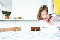 Girl (5-6) sitting at table with bowl and box of cereal