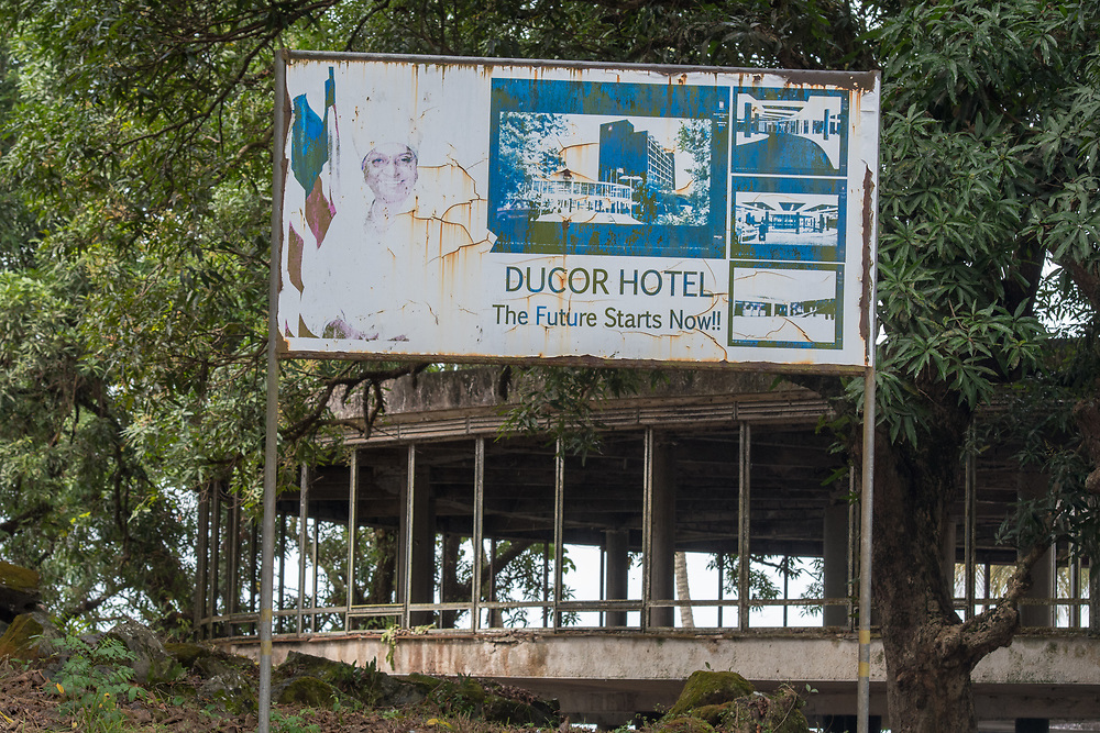A sign stands outside of the abandoned Ducor Hotel advertising its features, once the most prominent hotels in Monrovia, Liberia.