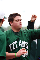 28 April 2012:  Kevin Callahan gets high fives after crossing home plate to complete a 3 run blast over the right field fence during an NCAA division 3 Baseball game between the Augustana Vikings and the Illinois Wesleyan Titans in Jack Horenberger Stadium, Bloomington IL